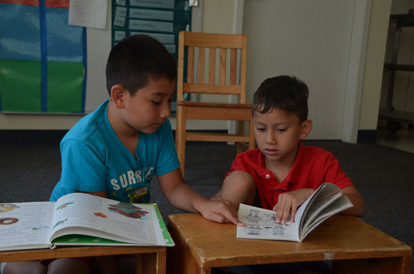 Two young children looking at books