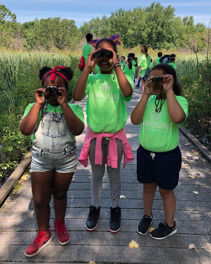 Three Horizons students holding binoculars